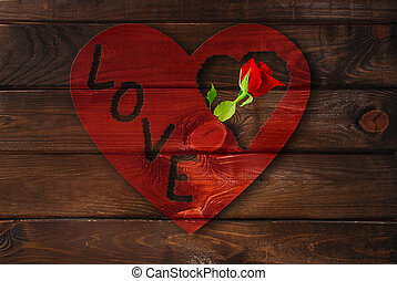wooden background with red heart and rose