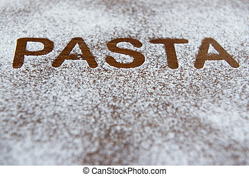 wooden background with sprinkled flour and the word pasta written