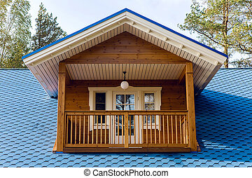 wooden balcony in a small house with  blue roof