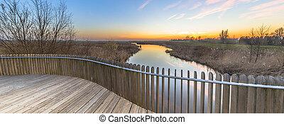 Wooden balustrade sunset over swamp