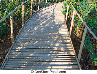 Wooden bamboo path way with beautiful flowers in the park.