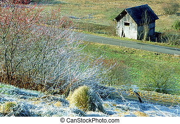 Wooden barn (grangette), frost and road in countryside in Bauges, Savoy. France