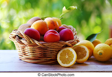 wooden basket of ripe fruits on table