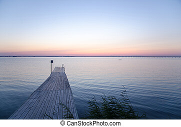 Wooden bath pier at soft colored sunset