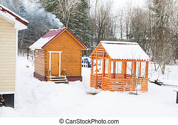 Wooden bath with a gazebo outside the city in winter