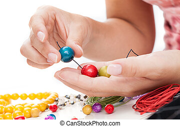 A closeup of hand stringing colorful wooden beads on a thong