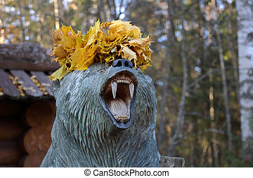 Wooden bear with autumn leaves