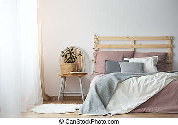 Wooden bed in bedroom - Wooden bed with bedding in cozy grey...