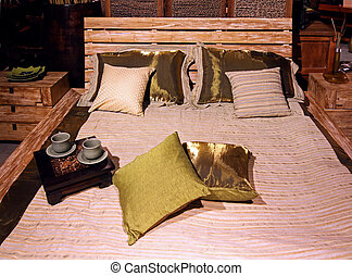 Wooden bed in bedroom interior with small tray