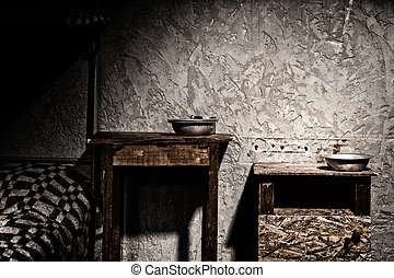 Wooden bedside tables with aluminum dishes in empty dark jail cell