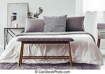 Wooden bench against white bed