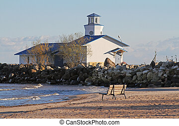 Wooden bench and lighthouse on the shore of Lake Ladoga