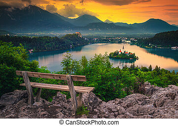 Wooden bench and stunning view with lake Bled at sunrise