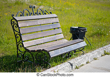 Wooden bench for rest and garbage bin in a city park.