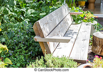 Wooden Bench in a wildflower garden. with green plants and colorful flowers with sunlight