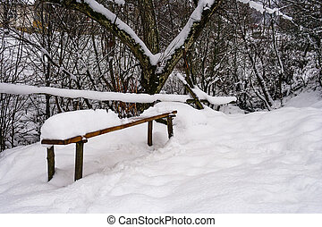 wooden bench in snowy outdoors. lovely winter scenery in...