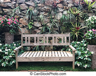 Wooden bench in the garden over granite stone wall and creeper background