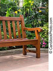 Wooden bench in the tropical garden