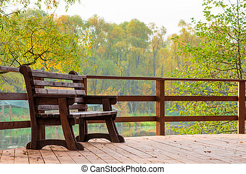 Wooden bench on a bridge over a lake in an autumn park