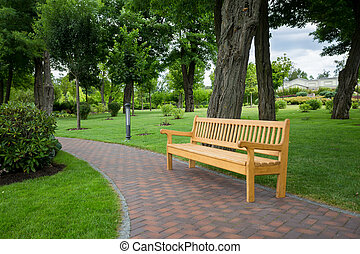 Wooden bench on path at park