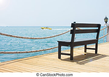 Wooden bench on the pier by the sea with a boat