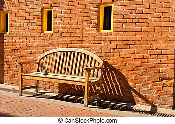 Wooden Bench Sitting by Orange Brick Wall with Yellow Windows