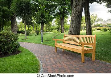 Wooden park bench under trees