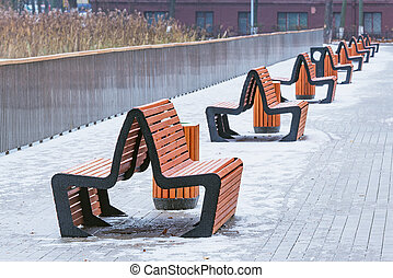 Wooden benches in the city park at winter day.