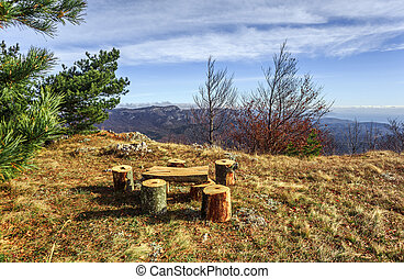 Wooden benches, table and bonfire site on the glade near pine tree at autumnal mountain landscape under blue cloudy sky.