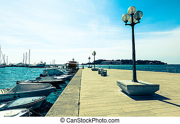 wooden berth with street-lamp on sea background. Pula Croatia