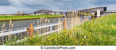 Modern wooden bridge Pieter Smit brug in Blauwestad in Oldambt Groningen in the The Netherlands which connect the newly build city Bauwestad with Winshoten. Longest bicycle bridge of Europe.