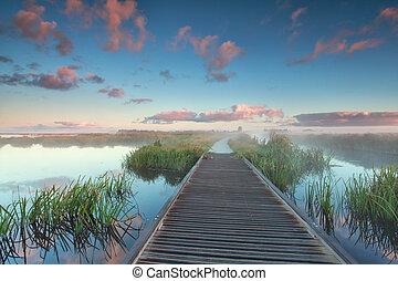 wooden biking road on water at sunrise
