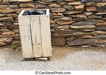 Wooden bin and slate stone wall background