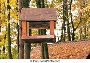 Wooden bird feeder in the autumn park
