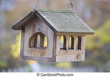 Wooden bird feeder in the form of a house.