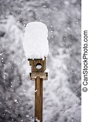 Wooden bird feeder with a tall cap of snow standing in a winter garden