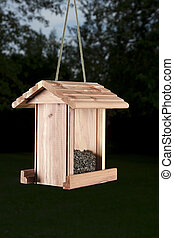 wood bird feeder against a wooden area background