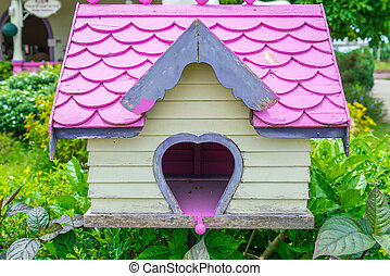 Wooden bird house in park .