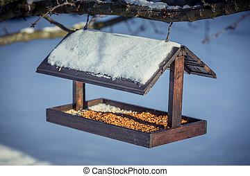 Wooden Birdfeeder on a tree in winter - Birdfeeder on a tree...