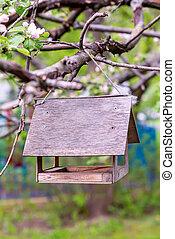 wooden birdhouse bird feeder side view hanging on a branch