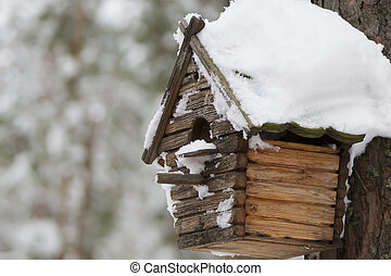 Wooden birdhouse. House for birds in the winter forest
