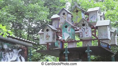 Wooden birdhouses in the park - In the park behind the fence...