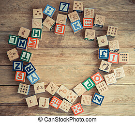 Wooden block alphabet lay on wooden floor in circle shape
