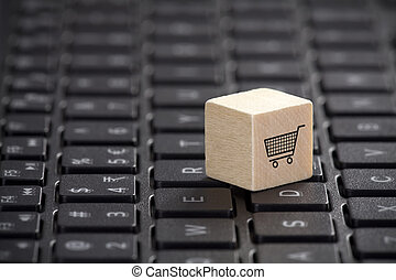 Wooden block with shopping cart graphic on laptop keyboard. Online shopping concept.