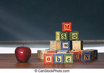 Wooden blocks and apple on desk