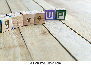 Wooden blocks are Give up word on wooden floor