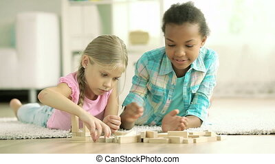 Wooden blocks of dream - Pretty girls building structures...