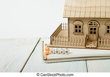 Wooden blocks spelling the word LOAN and model house on table