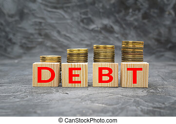 Wooden blocks with the word debt and money coin stack on dark background. Financial debt decrease concept.