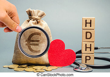 Wooden blocks with the word HDHP and money bag with euro sign. High-deductible health plan concept. Health insurance plan with lower premiums and higher deductibles than a traditional health plan